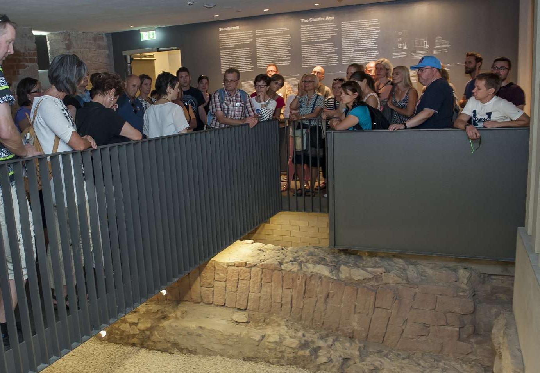 Besucher des Museums betrachten alte Grundmauern des Saalhofs