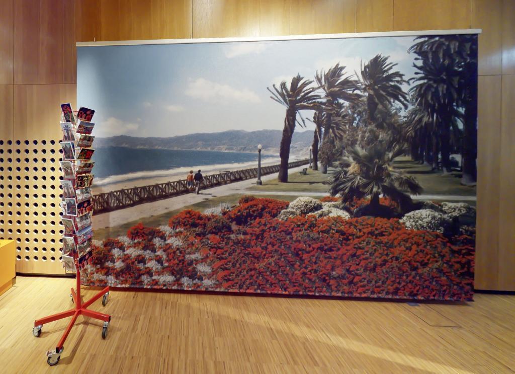 Blick in die Ausstellung auf ein riesiges Bild mit Geranien und Meer