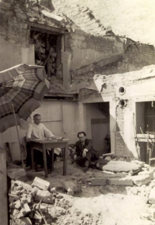 Zwei Männer sitzen vor einem kriegszerstörten Haus. Einer sitzt an einem Tisch unter einem Sonnenschirm, der andere im Schneidersitz auf der Erde.