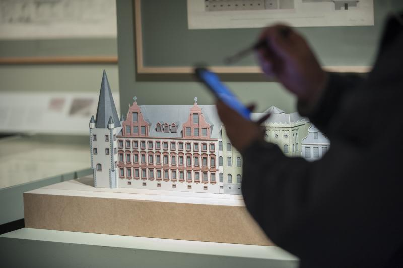 Ein Foto zeigt ein Modell des Museums und eine Person, die etwas in ihr Smartphone tippt