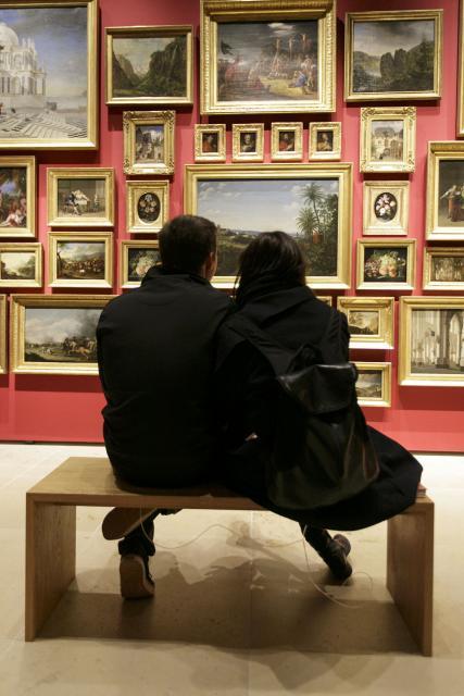Ein Foto zeigt ein kuschelndes Paar auf einer Bank vor den Gemälden in der Sammlung Daems