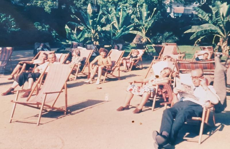Menschen sonnen sich in der Grossstadt, Bananenpalmen im Hintergrund