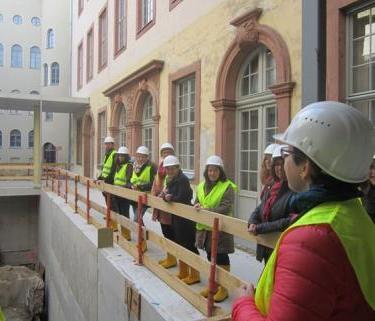 Ein Foto zeigt eine Gruppe mit Sicherheitskleidung auf der Baustelle