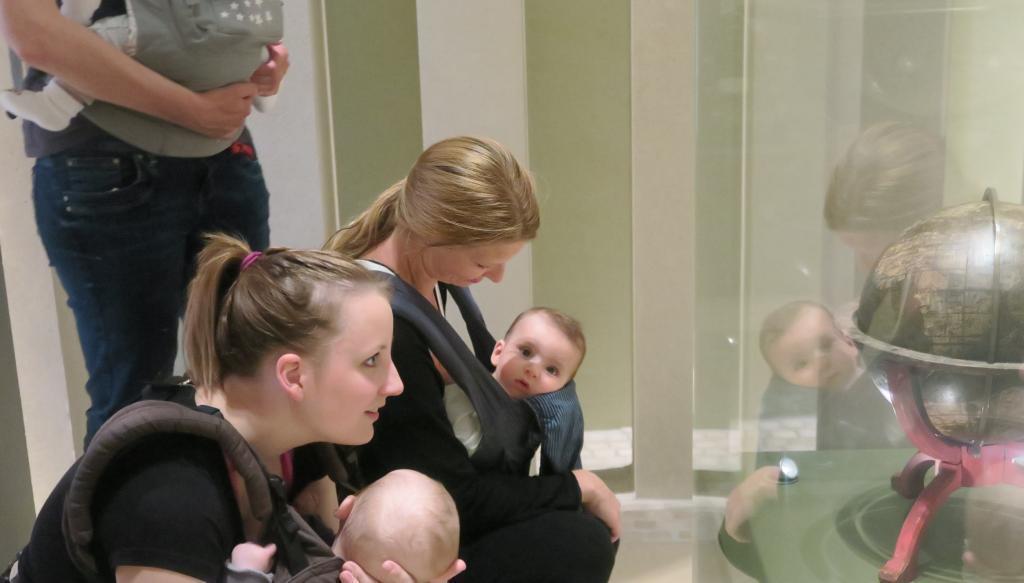 Auf dem Bild sieht man eine Gruppe von Müttern mit Kleinkindern, die fasziniert in eine Vitrine blicken. (c) HMF