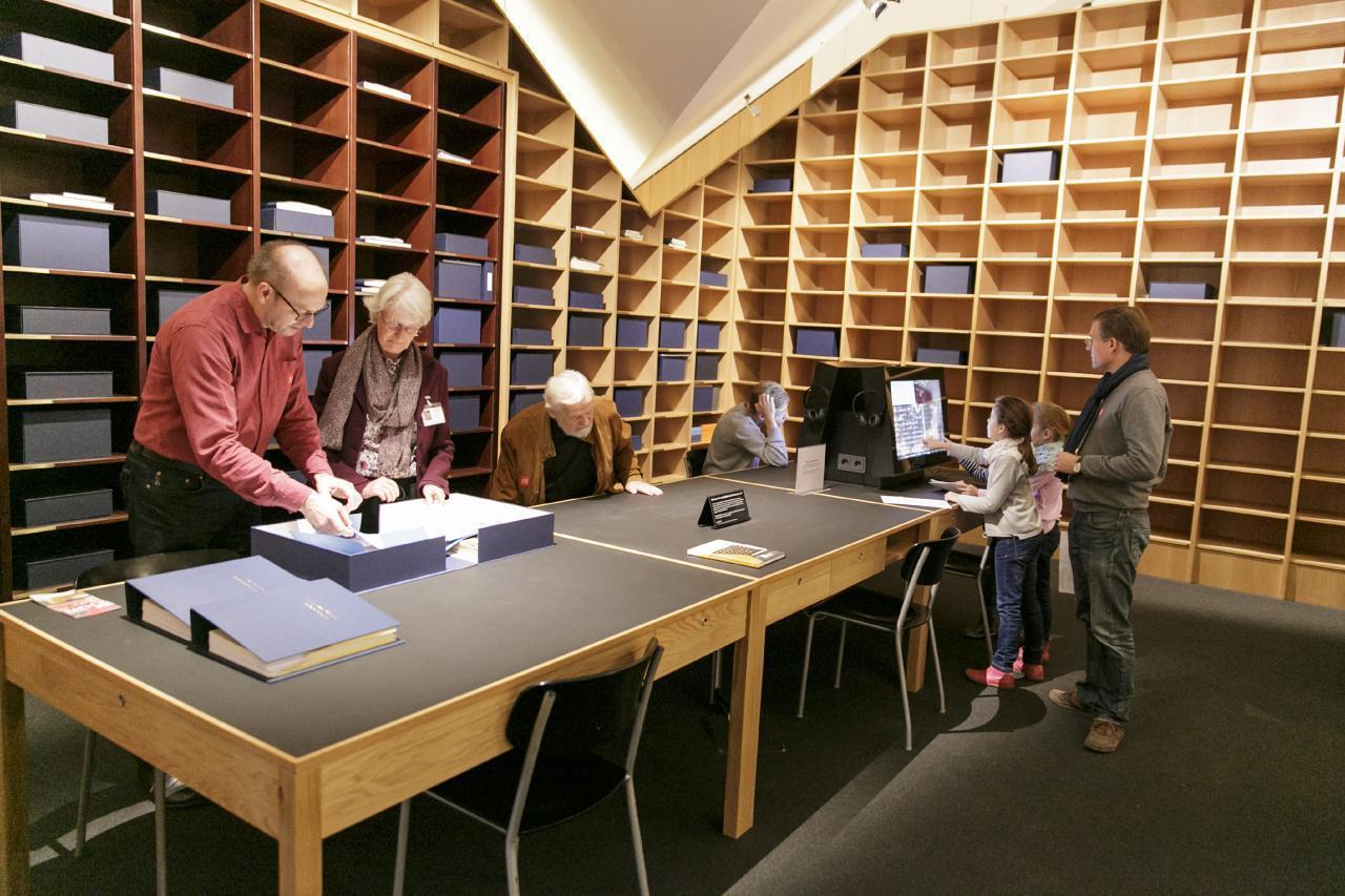 Ein Foto zeigt Besucher*innen in der Bibliothek der Generationen, die in einer Kassette einen Beitrag anschauen und an der Medienstation recherchieren.