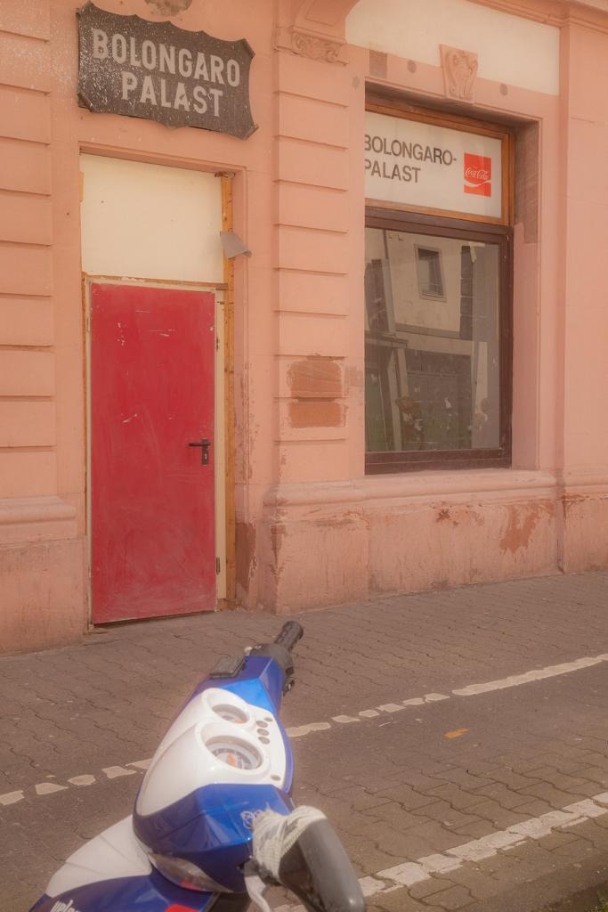Das Foto zeigt eine Gebäudefassade direkt neben dem Bolongaropalast mit einer roten Tür, einem Fenster und zwei Tafeln mit der Aufschrift