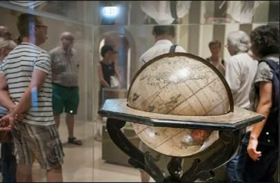 Das Foto zeigt einen Globus aus der Sammlung Waldschmidt und eine Gruppe darum herum